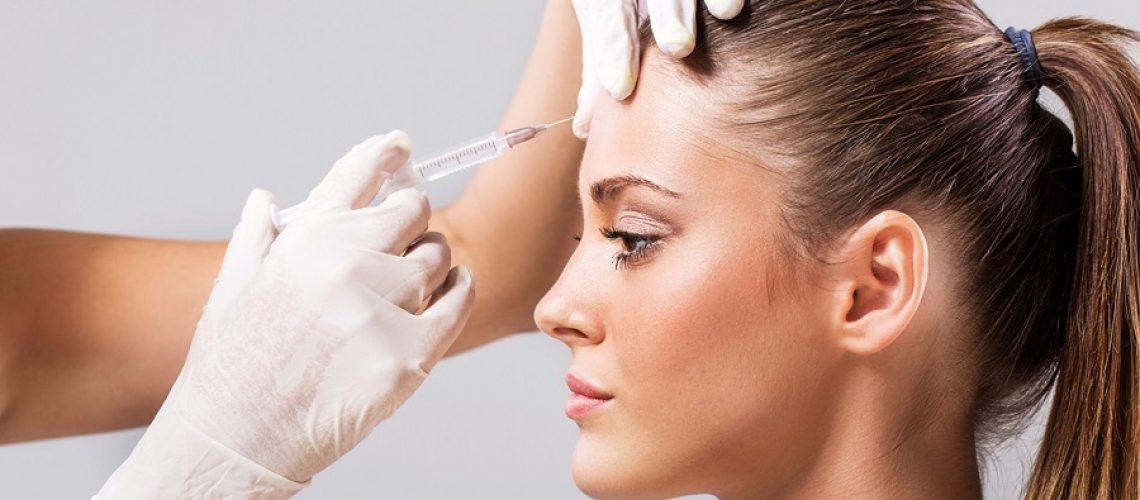 Side view of a young woman receiving botulinum toxin injection.