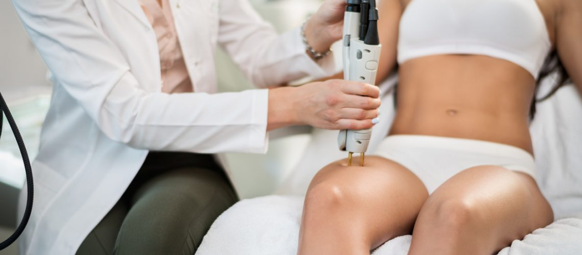 Young woman is having leg hair removal treatment with medical laser.