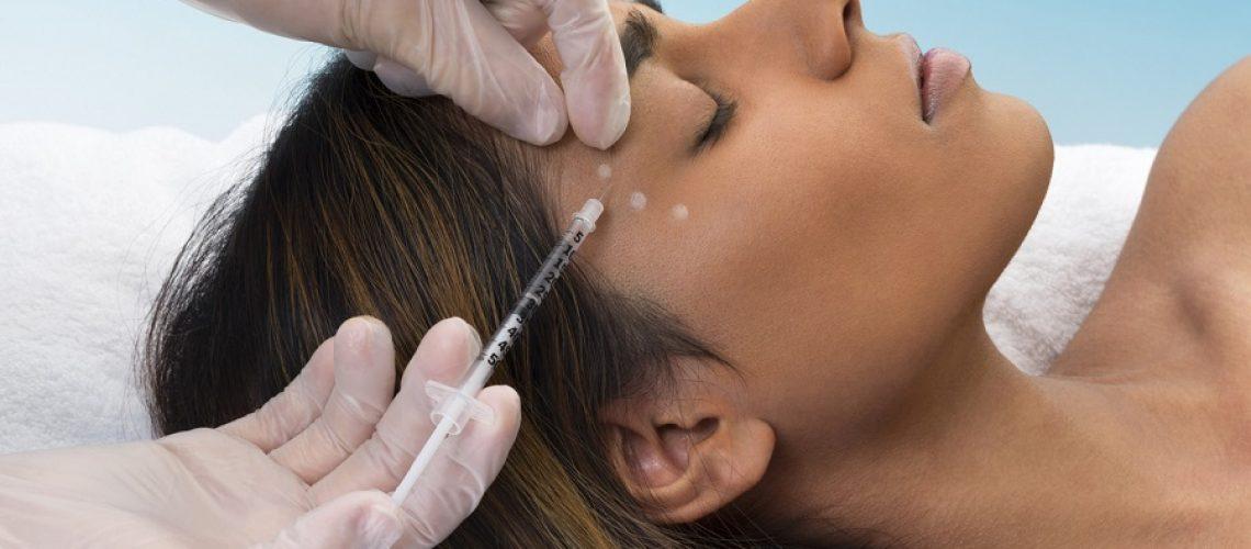 Young mixed race woman lying down receiving botox injection.